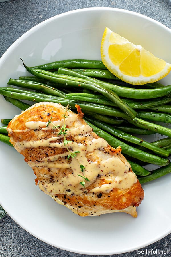 overhead picture of sauteed chicken breast drizzled with creamy mustard sauce, next to roasted green beans and lemon wedge on white plate