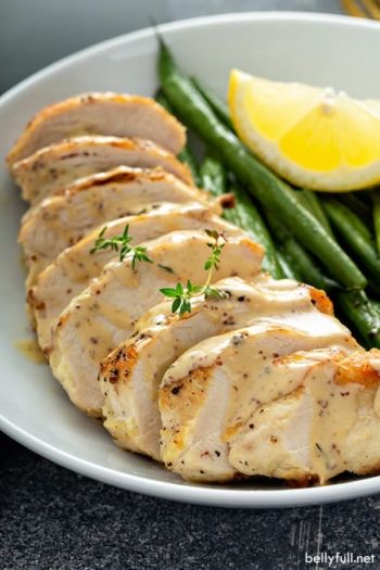 sliced cooked chicken breast with mustard cream sauce on white plate