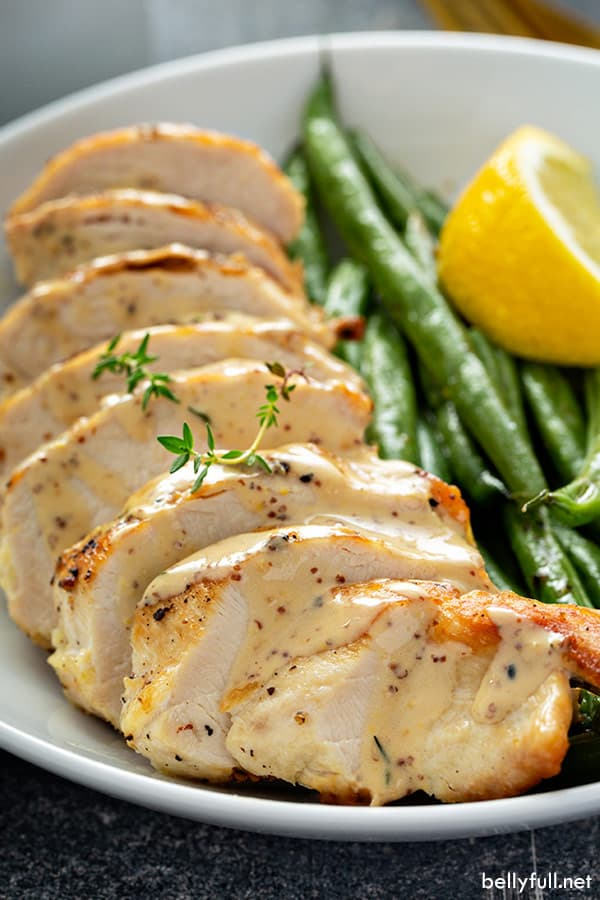 close up picture of sauteed sliced chicken breast with creamy mustard sauce