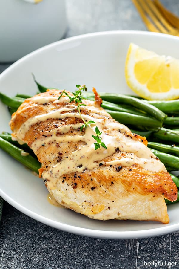 sauteed chicken breast with mustard cream sauce drizzled on top, on white plate with roasted green beans