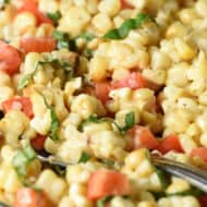 close up picture of creamy corn salad in glass serving bowl with serving spoon