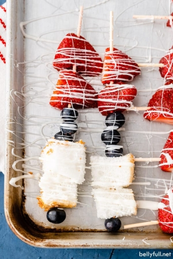 overhead dessert kabobs on baking sheet made with blueberries, strawberries, and angel food cake, drizzled with white chocolate
