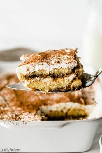Piece of Tiramisu dessert on metal serving spoon over white casserole dish