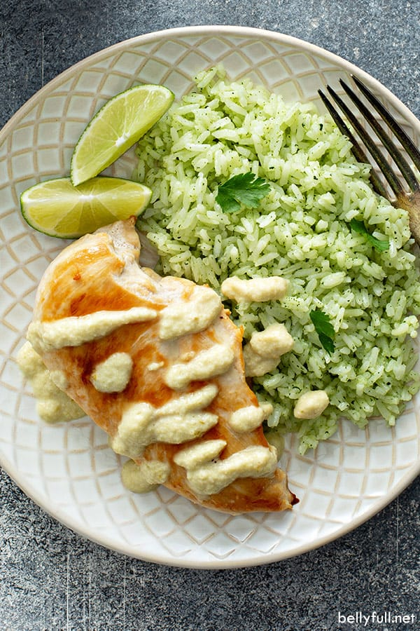 overhead picture of pan fried chicken breast with creamy chile sauce and cilantro lime rice on white patterned plate
