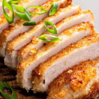 close up picture of sliced panko crusted boneless pork loin chops on cutting board