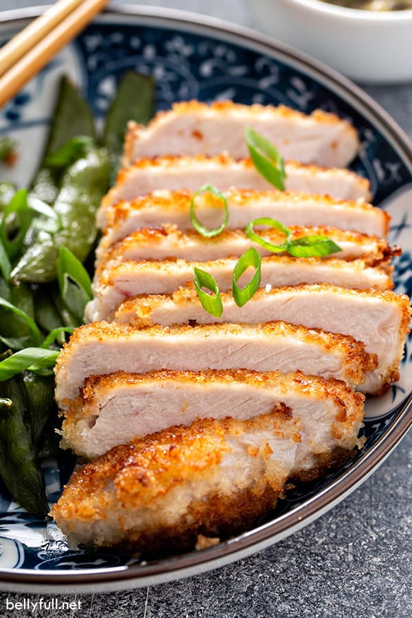 sliced panko breaded pork loin chops on plate with diced scallions