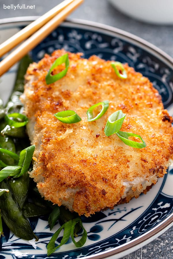 close up picture of panko-crusted pork chop on ornate plate with chopsticks