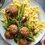 close up overhead picture of cooked turkey meatballs, green beans, mushrooms, and bowtie pasta on white plate