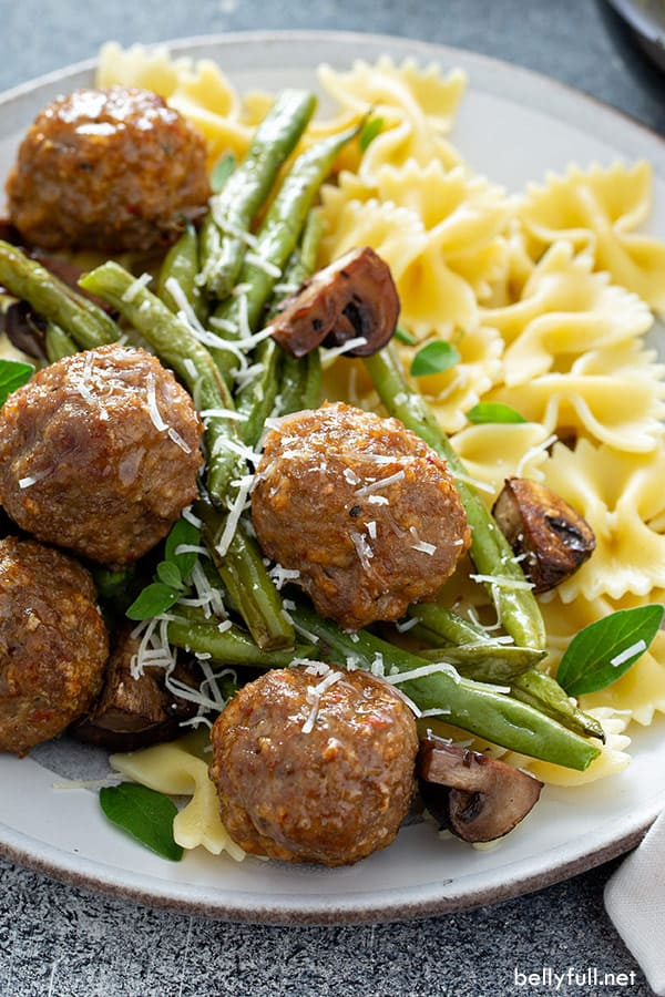 close up picture of cooked ground turkey meatballs with green beans, mushrooms, and pasta on white plate