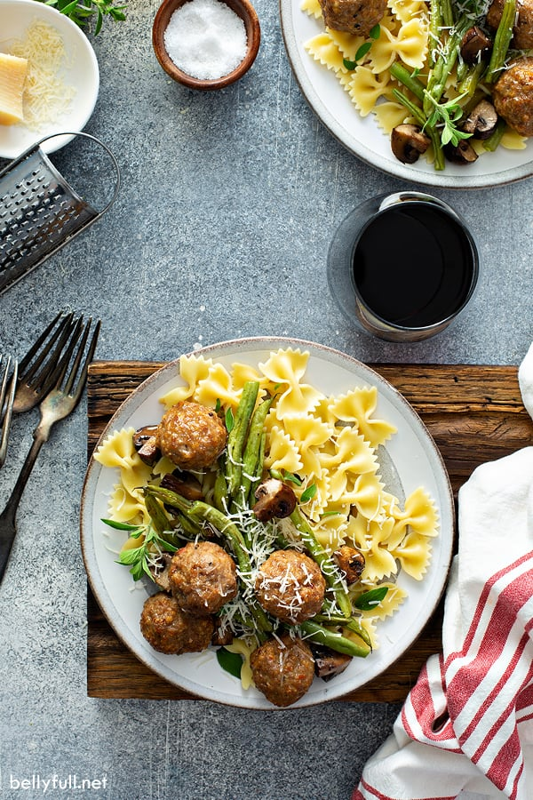 overhead picture of cooked turkey meatballs, green beans, mushrooms, and bowtie pasta on white plate