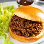 sloppy joe sandwich on white plate with lettuce