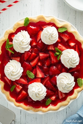 overhead picture for whole strawberry pie with dollops of whipped cream and mint leaves