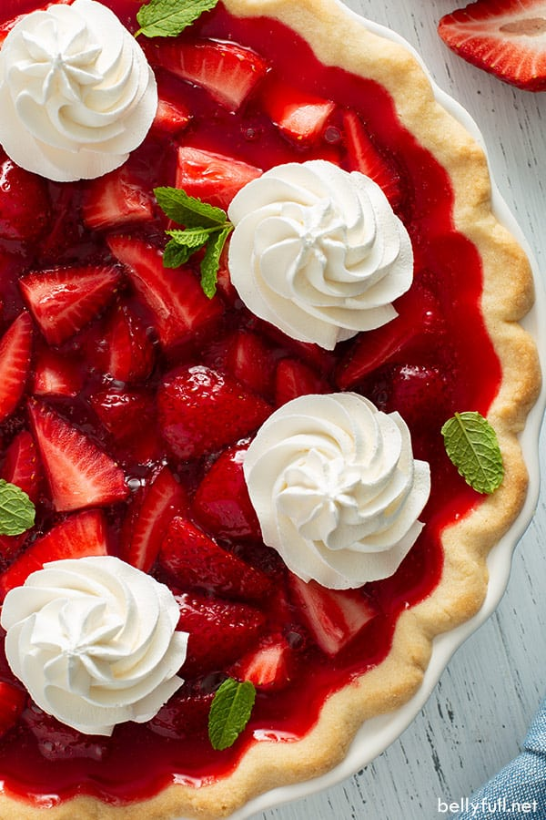 close up overhead picture of whole strawberry pie with mounds of whipped cream
