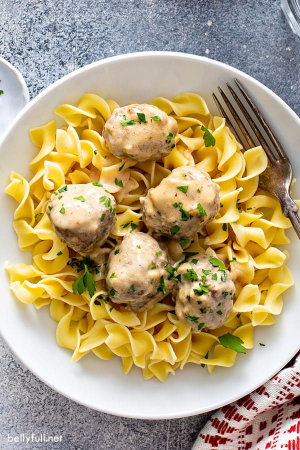close up overhead picture of Swedish meatballs on top of egg noodles in white bowl with fork