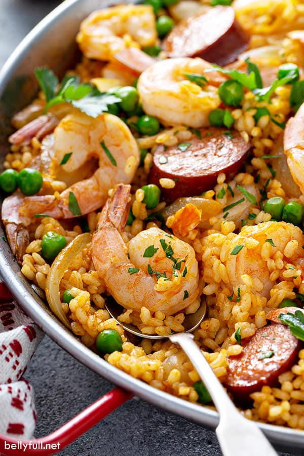 close up picture of shrimp paella on spoon in skillet