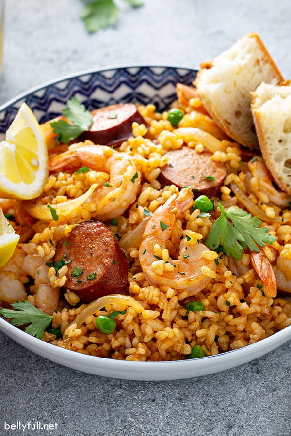 Spanish paella with chorizo and shrimp in ornate bowl with rustic bread