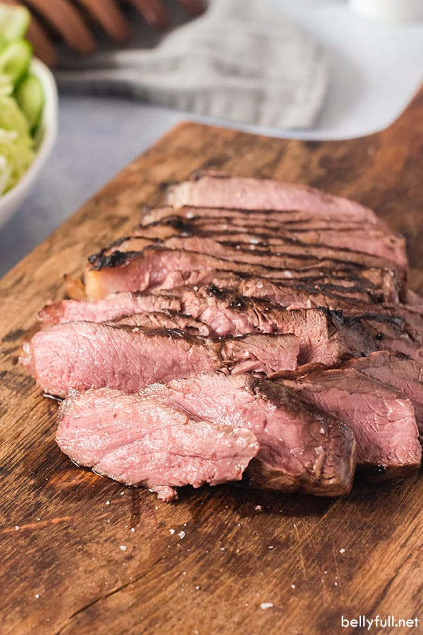 sliced grilled steak on cutting board