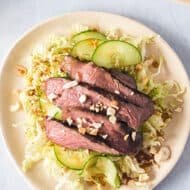 overhead of sliced grilled steak on top of cabbage and cucumber salad on off white plate