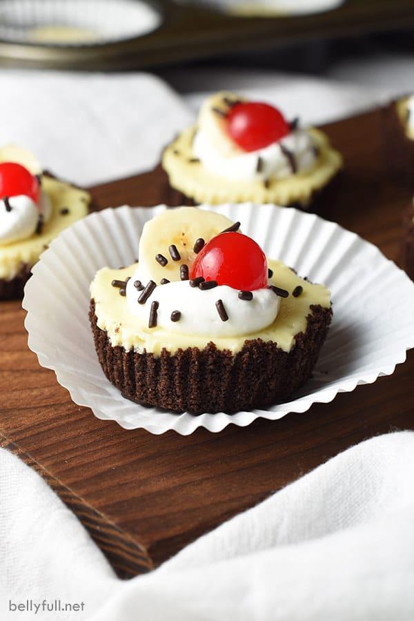 mini banana split cheesecakes in white muffin tin liner on cutting board
