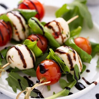 close up of 3 caprese skewer appetizers on white plate