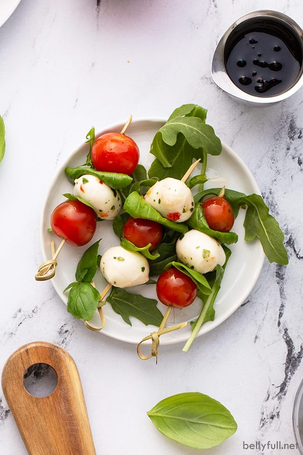 overhead picture of 3 Caprese skewers on white plate