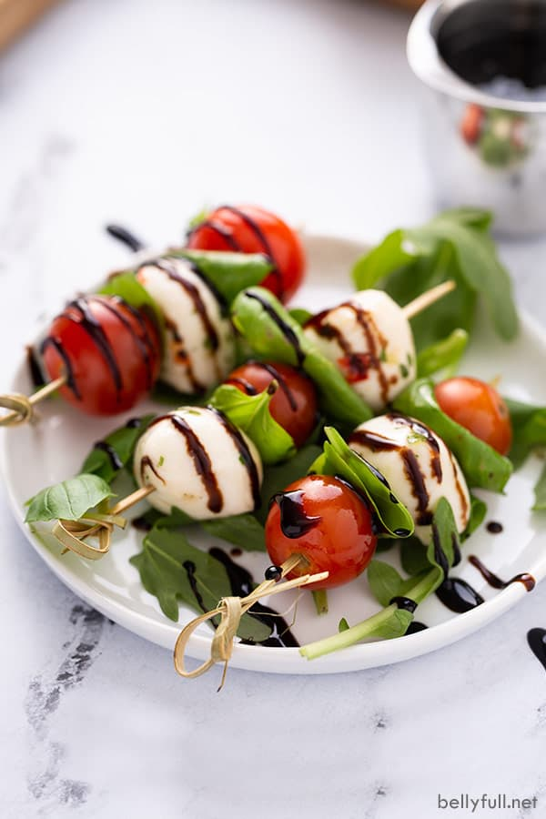 3 caprese skewers on white plate