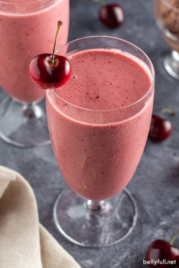 overhead angle of tall glass filled with cherry smoothie with fresh cherry on rim
