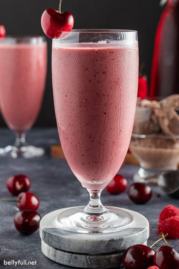 tall cold glass filled with chocolate cherry smoothie with fresh cherry on top