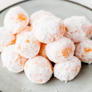 mound of powdered sugar coated orange chocolate truffles on plate