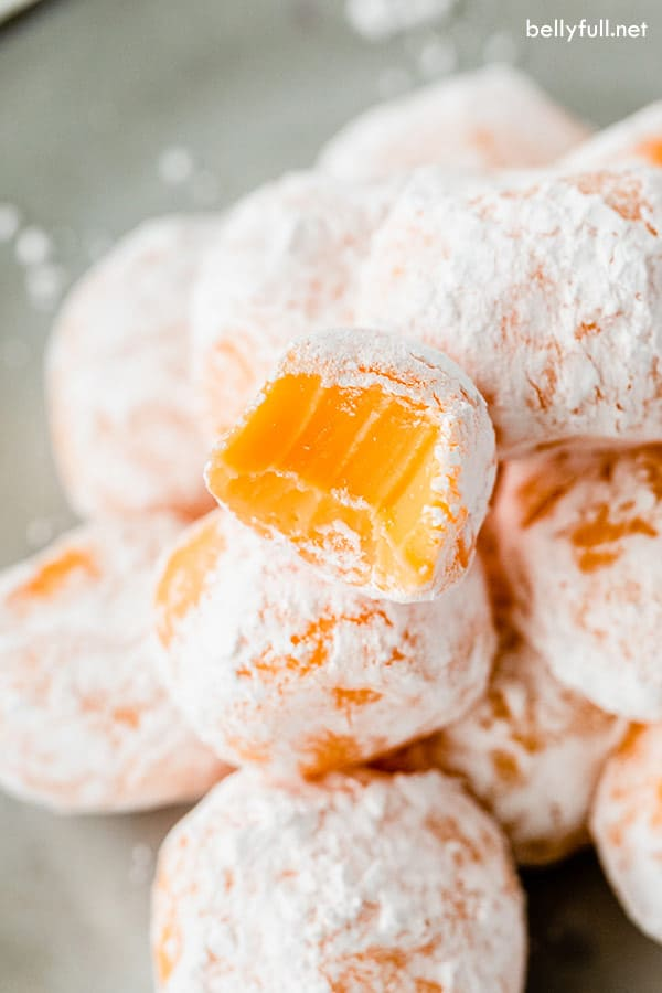 orange chocolate truffle coated in powdered sugar with a bite