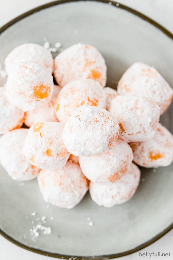 overhead pile of orange chocolate truffles coated in powdered sugar on silver plate
