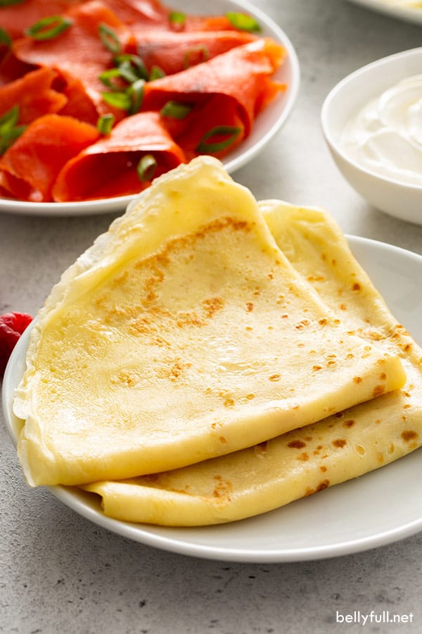 2 folded crepes on top of one another on white plate with condiments in the background