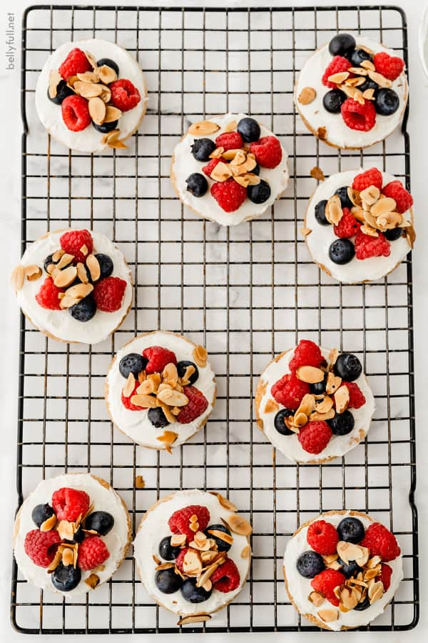 overhead of mini fruit tarts with raspberries and blueberries on cooling rack