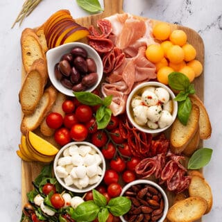 overhead of rectangular meat and cheese board with mozzarella balls, cured meats, fresh peaches, and cherry tomatoes