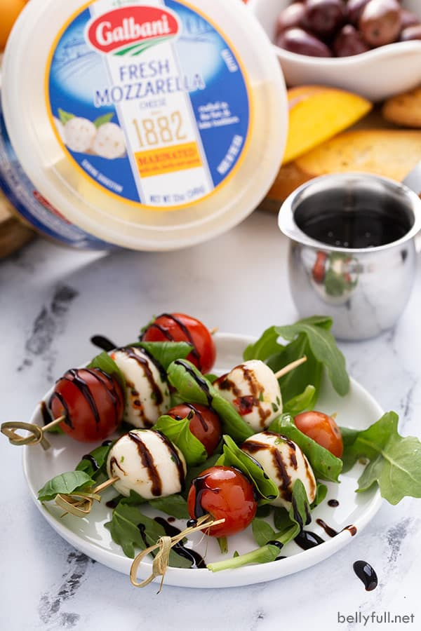 caprese appetizer skewers drizzled with balsamic glaze on white plate