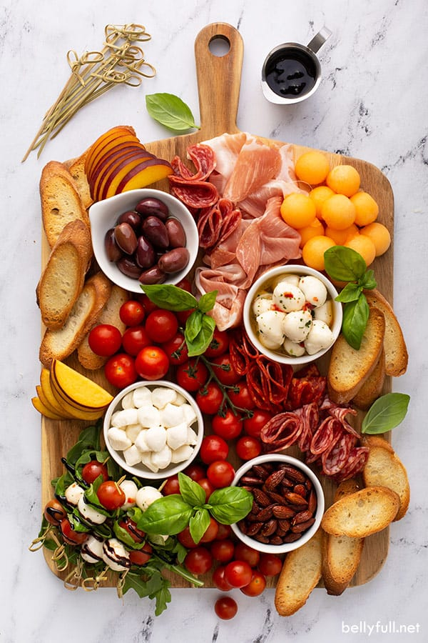 overhead of rectangular anitpasto charcuterie board with mozzarella balls, cured meats, fresh peaches, and cherry tomatoes