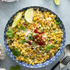 overhead of mexican corn salad recipe with lime wedges and cilantro leaves