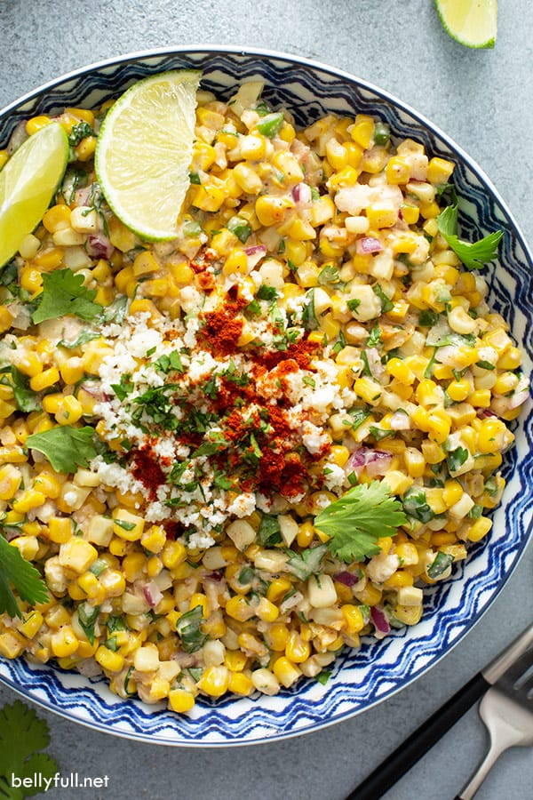 overhead of Mexican Street Corn in ornate bowl with lime wedges