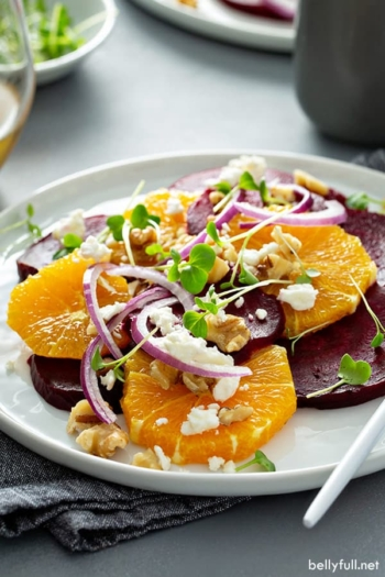 orange beet salad with red onion, feta cheese, and walnuts on white plate
