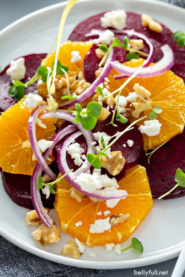 close up picture of orange beet salad on white plate