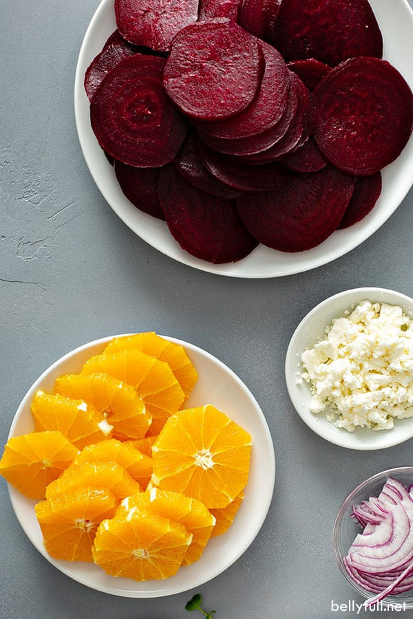 picture of sliced oranges, roasted sliced beets, and crumbled feta cheese in white bowls
