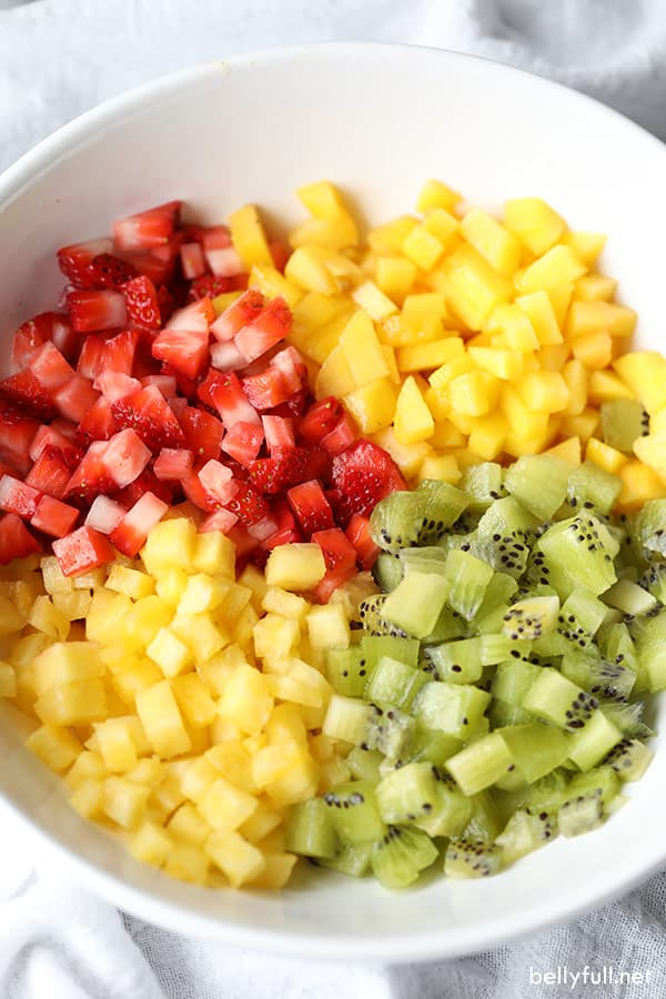diced up strawberries, kiwi, pineapple, and mango in a white bowl
