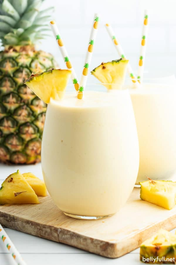 pineapple smoothie in glass with pineapple wedge and pineapple decorated straws