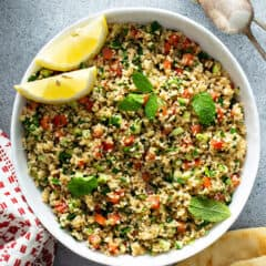 overhead picture of Tabbouleh in white bowl with lemon wedges