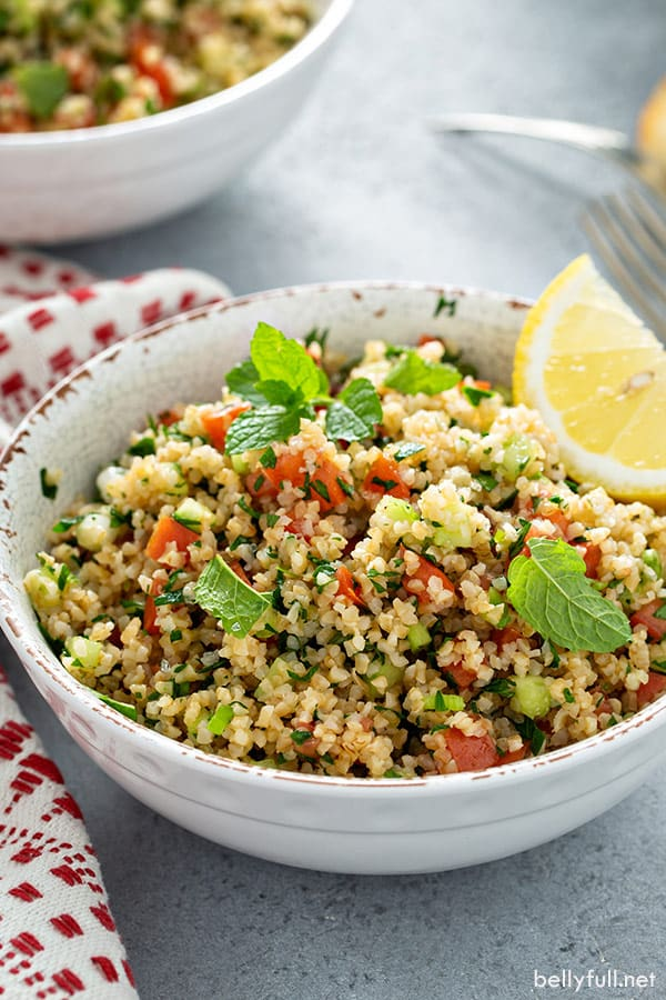 portion of Tabbouleh in white bowl with lemon wedge