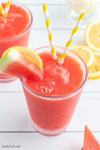 watermelon slushie in tumbler glass with yellow and white striped straw and garnished with watermelon slice