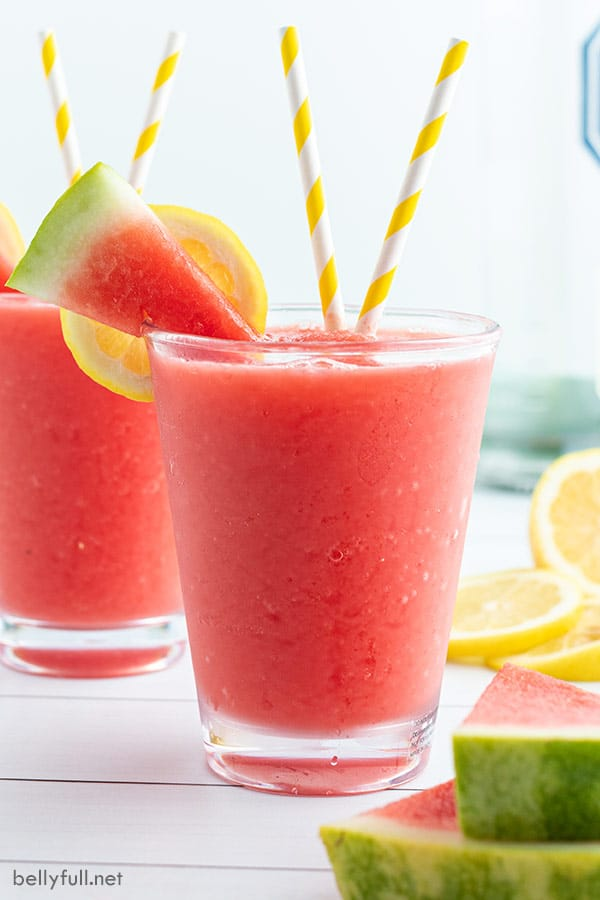 watermelon slushie in short glass tumbler with yellow and white striped straws