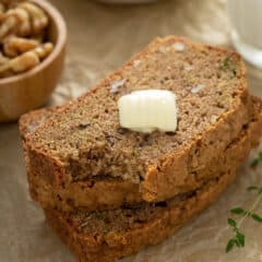 3 stacked slices of zucchini bread with bite from one and a pat of butter on top