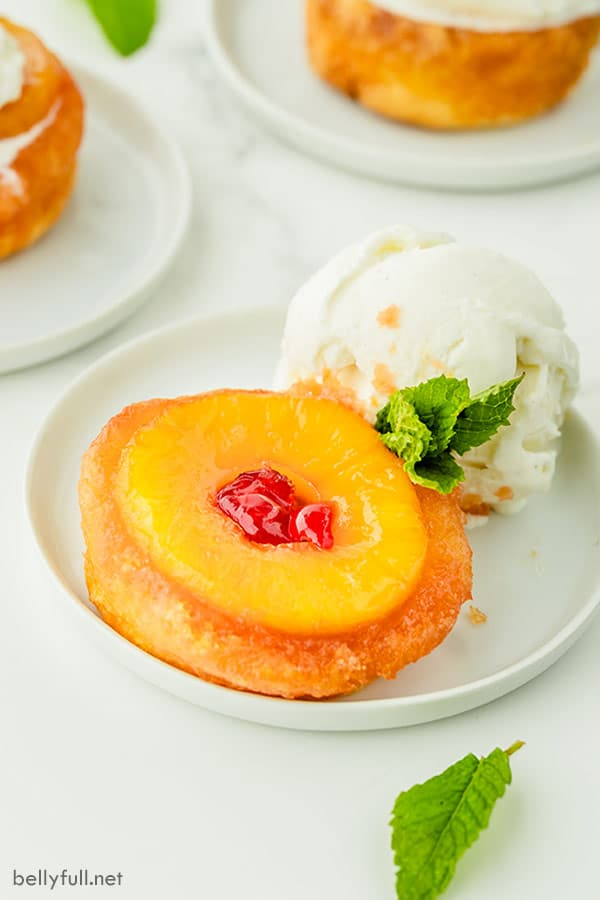Individual Pineapple Upside Down Cake dessert shell on white plate with vanilla ice cream and fresh mint leaf