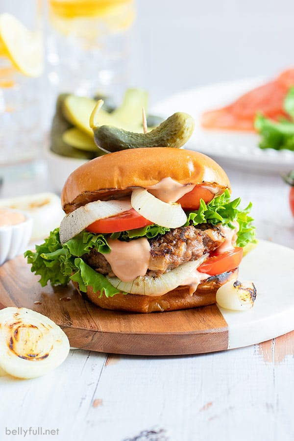 onion burger on bun with onion, tomato, lettuce, and dressing